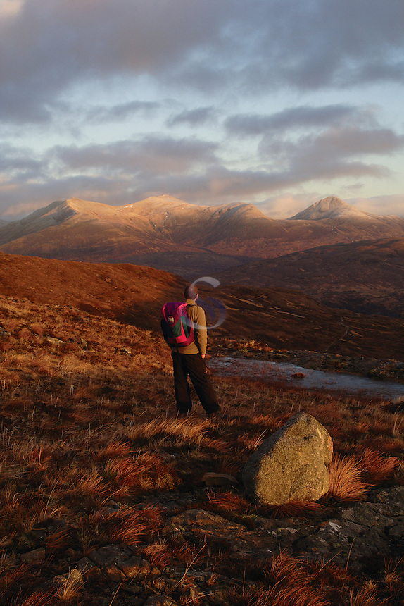 A walker looking to the Mamores at dawn from Stob Mhic Mhartuin above Glencoe, Highland<br /> <br /> Copyright www.scottishhorizons.co.uk/Keith Fergus 2011 All Rights Reserved