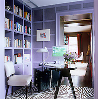 The home office is furnished with a retro black lacquered kidney-shaped desk and filing cabinet on a zebra-stripe rug