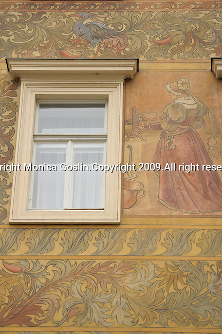 A painted building in Prague, Czech Republic. A building in Prague with elaborate paintings of people, birds, and florals.