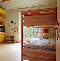 Simple wooden bunk beds leave ample room to play in this child's bedroom