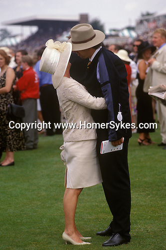 Couple hold each other and kiss at Glorious Goodwood horse races Sussex