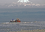 BOAT LAUNCHING ALASKAN STYLE.  Fishermen being launched by Beachmaster's Tractor at Anchor Point beach, Cooks Inslet,  Mount Illamna on north side of Inslet in the backgound. Beachmaster controls all launching and recoveries.