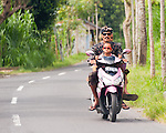 A Balinese family returning from temple -- seen on the road in Bali, Indonesia.  Motor scooters are common and preferred transportation on Bali; it is not at all uncommon to see an entire family on a single bike.  Judging from the formal traditional apparel, this family seems to be coming from or going to a traditional Balinese Hindu temple.