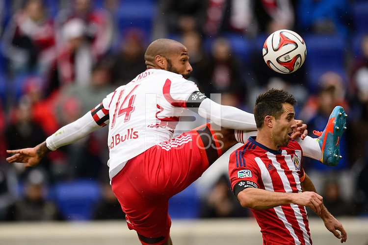 Thierry Henry (14) of the New York Red Bulls attempts to play the ball past Carlos Bocanegra (3) of Chivas USA. The New York Red Bulls and Chivas USA played to a 1-1 tie during a Major League Soccer (MLS) match at Red Bull Arena in Harrison, NJ, on March 30, 2014.