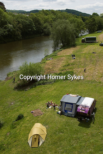 Festival goers camp by the Wye river. The Hay Festival, Hay on Wye, Powys, Wales, Great Britain. 2006.