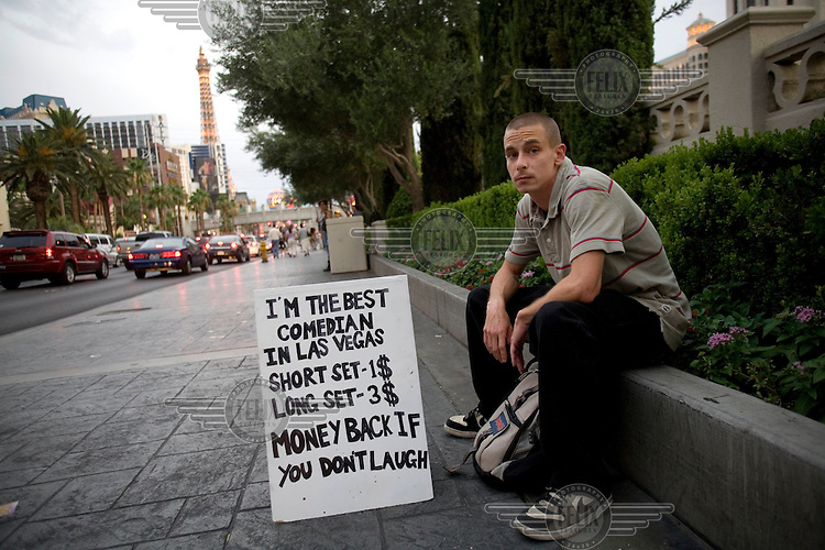 A young man sits with a billboard that advertises his skills as a comedian for hire on the 'Strip', in Las Vegas, Nevada.