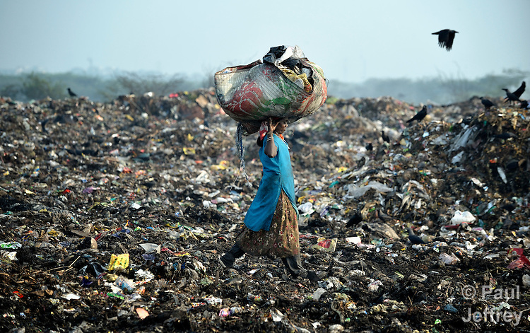 A woman scavenges for recyclable items in the smoldering municipal garbage dump in Chennai, India.