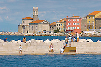 Harour entance with people relaxing and swimming off the harbour wall. Piran , Slovenia