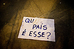 A sign reads: What country is this, a sentence from a famous Brazilian song about politics in Brazil, in Rio de Janeiro, Brazil, on Thursday, June 20, 2013. About 300,000 Cariocas (residents of Rio de Janeiro) protest downtown against the government, which began with a 20-cent hike in public transport fares, and moved to widespread frustration about a heavy tax burden, corrupt politicians and weak public education, health and transport systems, as the nation hosts the Confederations Cup soccer tournament and prepares for next month's papal visit.<br /> <br /> The demonstrations came despite the government's U-turn over public transport fare hikes which sparked the protests over a week ago.