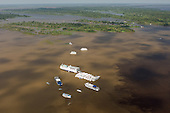 Manaus, Brazil. Meeting of the Waters of the Solimoes (Amazon) and Negro Rivers (Encontro das Aguas). Tourist boats gathered next to the division between the black waters of the Negro River and the white waters of the Amazon (Solimoes).