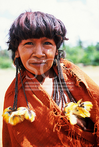 Ipixuna Village, Para State, Brazil. Arawete Indian woman in red wrap shawl with feather and bead hair decorations.