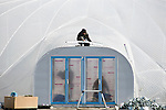 Workers assemble the entranceway to the greenhouse domes  at the Minamisoma Agri-Solar Park in Minamisoma, Fukushima, Japan on 10 Feb 2013. More than 2,000 solar panels will power the domes, inside which farmers affected by the 2011 tsunami and nuclear accident will be able to grow produce. Excess power will be sold to a local utilities company. .Photographer: Robert Gilhooly