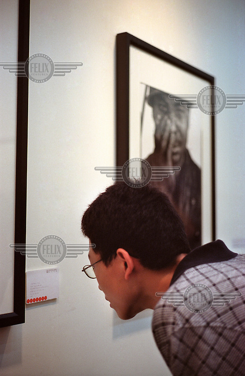 A visitor studies an information placard inside an art gallery in the Dashanzi Art District (also known as Factory 798). Many buildings in the former industrial area have been recently converted into fashionable art studios and galleries.