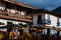 Colombian peasants sit in a coffee shop in front of the colonial houses at the main plaza of Jardín, a village in the coffee region (Zona cafetera) of Colombia, 29 November 2016.