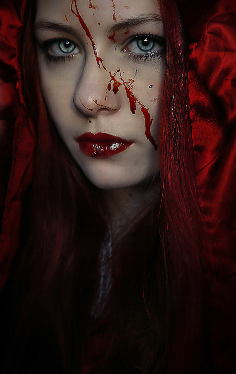A girl wearing a red hood with blood splattered on her face.