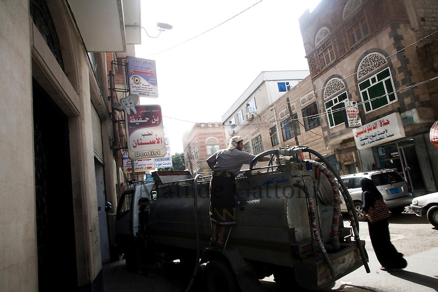 Yemen - Sana'a - Water trucks delivering water to the houses, water must be paid, hence very few houses can benefit of this service. Yemen's economy depends heavily on oil production, and its government receives the vast majority of its revenue from oil taxes. Yet analysts predict that the country's petroleum output, which has declined over the last seven years, will fall to zero by 2017. The government has done little to plan for its post-oil future. Yemen's population, already the poorest on the Arabian peninsula and with an unemployment rate of 35%, is expected to double by 2035..The trends will exacerbate large and growing environmental problems, including the exhaustion of Yemen's groundwater resources. Given that a full 90% of the country's water is used for agriculture, this trend portends disaster..Sanaa's well are expected to dry out by 2015, partly due to illegal drilling, partly because 40% of the city's water is diverted for qat production, and partly because conservation rules are difficult to enforce. Only 20% of the houses receive water, the other 80% has to collect it from pumps and wells. 15% of the urban population only uses bottled water as its primary drinking water source and that is why Yemen has one of the highest world mortality rate, most of the diseases being related to water..