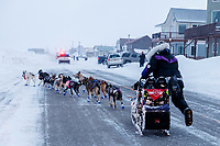 Jessie Royer runs down Front Street with a police car escort as she makes her way toward the Nome finish line to place 3rd in the 2019 Iditarod sled dog race.<br /> <br /> Photo by Jeff Schultz/  (C) 2019  ALL RIGHTS RESERVED