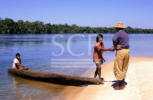 Amazon, Brazil. Ecotourist greeting a local Amazon Indian from a canoe on a sandy river bank.