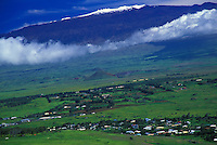 Snow capped Mauna Kea ringed by clouds, above Waimea town Big Island, Hawaii