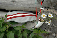 A grey felt bag decorated with a contrasting red and white stripe is displayed against the weathered wood of a rustic fence