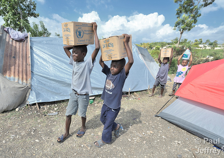 Children living in a camp for homeless families help unload food aid in Jacmel, a town on Haiti's southern coast that was ravaged by the January 12 earthquake.
