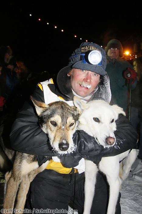 "Mitch Seavey hugs his leaders ""Payton"" and ""Ditka"" the finish line on Front Street after winning the  2008 All Alaska Sweepstakes Sled Dog Race, Alaska."
