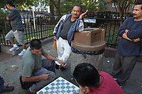 (171015RREI5537) La Esquina where Latinos have gathered for decades at the corner of Mt. Pleasant St. and Kenyon St. NW. to play chekers (damas). Jorge (green shirt), Oscar Hernandez (center).  Washington DC Oct. 15 ,2017 . ©  Rick Reinhard  2017     email   rick@rickreinhard.com