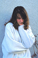 Distressed 14 year old girl thinking with chin on hand.  St Paul Minnesota USA