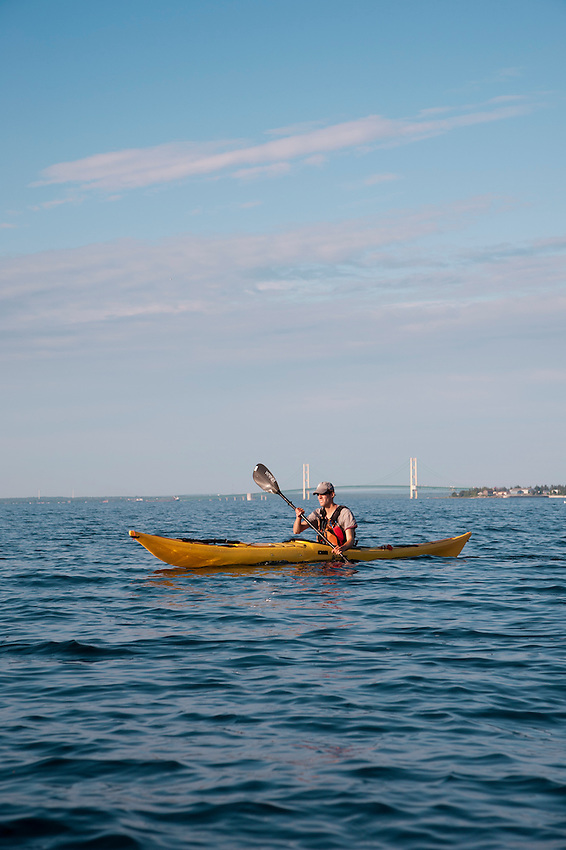 A kayaker is seen with the Mackinac Bridge while crossing the Mackinac Straits near Mackinac Island and St. Ignace Michigan.