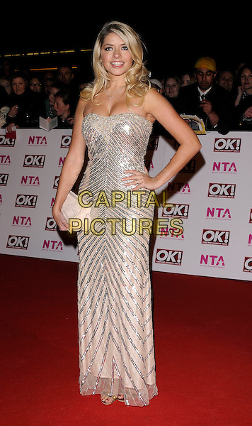 HOLLY WILLOUGHBY.The National Television Awards held at the Royal Albert Hall, London, England, 29th October 2008. .NTA red carpet arrivals full length strapless silver beaded beads sequins sequined dress shiny cleavage hand on hip beige clutch bag .CAP/CAN.©Can Nguyen/Capital Pictures.