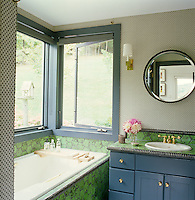 The walls of the master bathroom are covered in a polka dot wallpaper with hexagonal ceramic tiles around the bath and wash basin