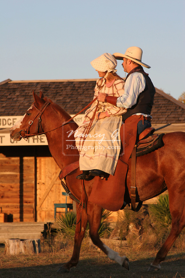 A young lady sharing a ride from a cowboy and his horse