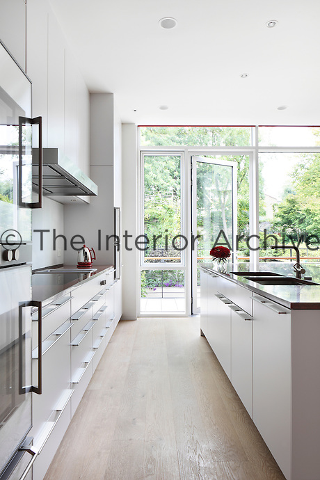 Modern white kitchen units with flat metal handles and red granite work surfaces of a Bulthaup kitchen