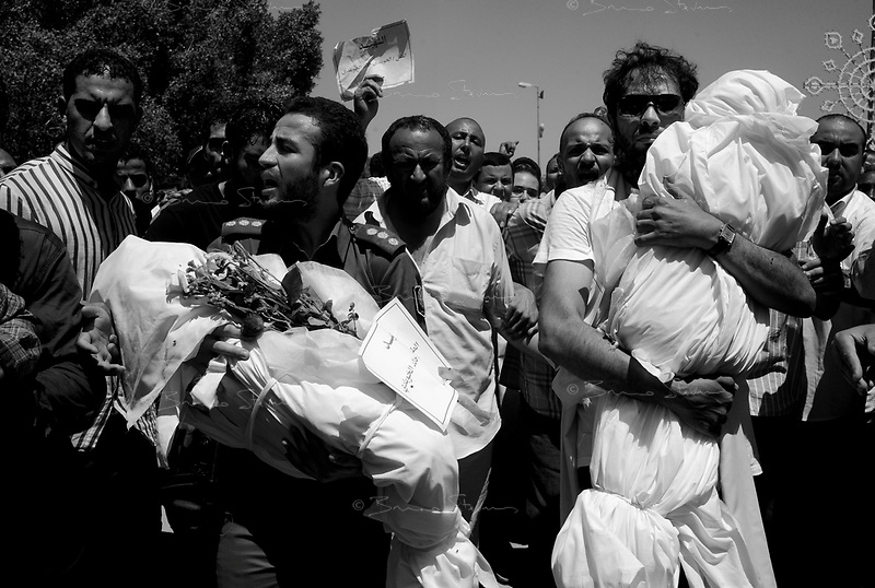 Surman, Libya, June 22, 2011.Mohammed (left) and Khaled (right), sons of Major General Khweidi Al Hamidi carry their dead children killed during a massive NATO night bombing of his large estate alledgedly used as a military control and command center.