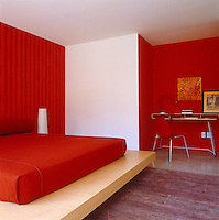 A red guest bedroom with a platform bed