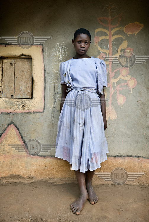 13 year old Rita Nabugibi stands beside the flowers she painted on the family home.