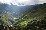 View across countryside with Trongsa Dzong on bottom left hand corner, towards mountain pass, Bhutan..Bhutan the country that prides itself on the development of 'Gross National Happiness' rather than GNP. This attitude pervades education, government, proclamations by royalty and politicians alike, and in the daily life of Bhutanese people. Strong adherence and respect for a royal family and Buddhism, mean the people generally follow what they are told and taught. There are of course contradictions between the modern and tradional world more often seen in urban rather than rural contexts. Phallic images of huge penises adorn the traditional homes, surrounded by animal spirits; Gross National Penis. Slow development, and fending off the modern world, television only introduced ten years ago, the lack of intrusive tourism, as tourists need to pay a daily minimum entry of $250, ecotourism for the rich, leaves a relatively unworldly populace, but with very high literacy, good health service and payments to peasants to not kill wild animals, or misuse forest, enables sustainable development and protects the country's natural heritage. Whilst various hydro-electric schemes, cash crops including apples, pull in import revenue, and Bhutan is helped with aid from the international community. Its population is only a meagre 700,000. Indian and Nepalese workers carry out the menial road and construction work.