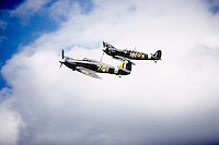 Spitfire and Hurricane flying together against a cloudy sky