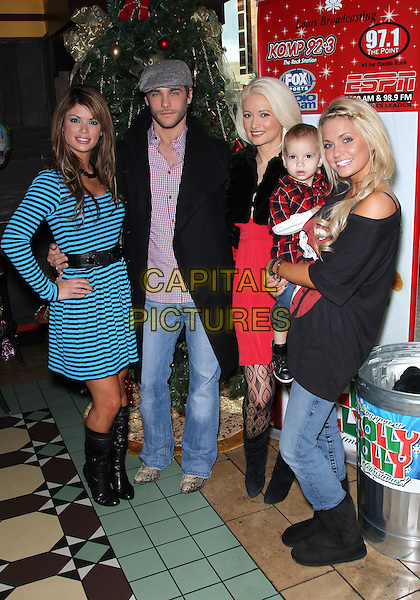 LAURA CROFT, JOSH STRICKLAND, HOLLY MADISON, ANGEL PORRINO & SON ROMAN.Holly Madison wraps up her Holly Jolly Toy Drive at El Segundo Sol Restaurant inside the Fashion Show Mall, Las Vegas, Nevada, USA, .18th December 2010..full length  black jacket smiling red dress fur patterned tights knee high boots baby son blue striped cap hat jeans uggs ugg boots .CAP/ADM/MJT.© MJT/AdMedia/Capital Pictures.