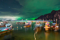 Photographer: Rick Findler<br /> <br /> THAILAND, Phi Phi Island: Long-tail boats sit under a green sky off the coast of Phi Phi Island. The green sky is from squid fishing boats which use florescent green light to attract squid.