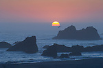 Sun setting into offshore fog bank at Harris Beach State Park, Oregon coast..#06061005