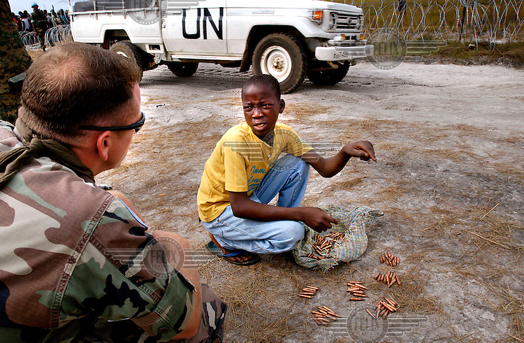 Disarmament process - a former child soldier hands in ammunition to an American soldier who asks him where and under whoÕs command he fought.   At the beginning of December, UNMIL (the United Nations peacekeeping force in Liberia) began to disarm the militias of former president Charles Taylor. The disarmament was marked by riots,  but after the UN decided to give 75 US Dollars to everybody who handed in a weapon, soldiers and child soldiers came in their thousands to the disarmament camps on the outskirts of Monrovia..