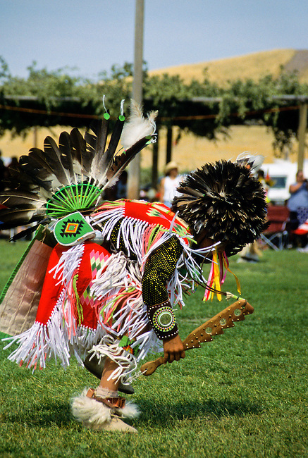 Young Cree dressed in traditional men's dance regalia wears an eagle feather mandan style headdress dances to the beat of drummers during a Chippewa Cree pow wow on the Rocky Boy Indian Reservation, Montana