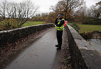 Pictured: A police officer stands on the bridge over river Ogmore near where Russell Sherwood went missing in Stormy Down, Wales, UK. Tuesday 22 November 2016<br />