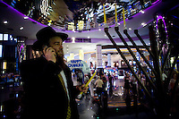 Chanuka candles on the stage as Rabbi Kantor speaks on his mobile just before giving a speech, during the Chanuka celebrations organised by Chabad Bangkok on 13th December 2009, at Paragon Mall's IMAX theater, Bangkok, Thailand..Photo by Suzanne Lee / For Chabad Lubavitch