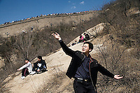 Tourists pose for pictures on a trail below the Great Wall at Badaling outside of Beijing, China.