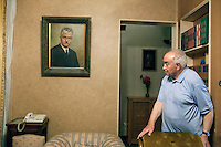 """Mohamed Hamed looks at his father's portrait in his apartment in Cairo. Mohamed, 84 years old, is a descendent of a four-generation doctors' family and is himself a cardiologist. In 2011, he published the """"Meaning of the Holy Qur'an"""", an accurate translation of the Koran that his father had started. July 27th, 2012. Cairo, Egypt."""