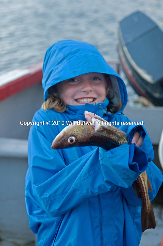young girl showing off the cod she caught