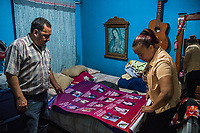 Carlos Saldana and Vicky Delgadillo pack away a poster showing the names and faces of their and other's missing children,  in the bedroom of their home in Xalapa, Mexico on November 4, 2017. <br /> Photo Daniel Berehulak for The New York Times
