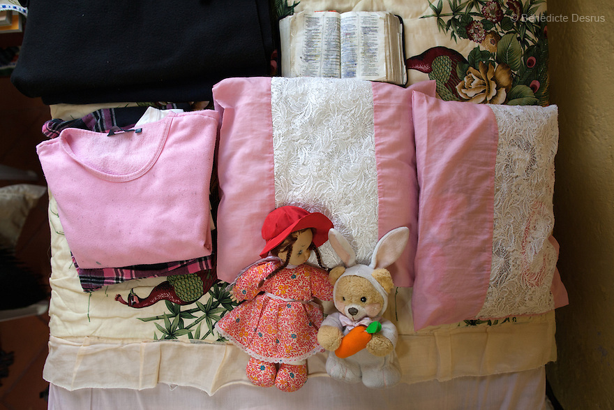 The personal belongings of Laeticia, a resident of Casa Xochiquetzal, in her bedroom at the shelter in Mexico City, Mexico on October 17, 2012.  At the age of 8, Leticia watched as her mother said goodbye from the back of a trailer. She never saw her again. Originally from Chihuahua, Mexico, Leticia began working at nightclubs and eventually married. She didn't walk out on her husband when he hit her—he made good money—but she did leave when he brought other women into their house. She abandoned everything, including her children, and has tried twice to commit suicide. At Casa Xochiquetzal, she practices yoga daily and tries to be a peacemaker and a good housemate; however, her sweet expression can quickly turn to anger. She stays active by knitting, embroidering, and reading the Bible. Casa Xochiquetzal is a shelter for elderly sex workers in Mexico City. It gives the women refuge, food, health services, a space to learn about their human rights and courses to help them rediscover their self-confidence and deal with traumatic aspects of their lives. Casa Xochiquetzal provides a space to age with dignity for a group of vulnerable women who are often invisible to society at large. It is the only such shelter existing in Latin America. Photo by Bénédicte Desrus